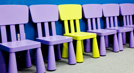 Yellow chair in the middle of several purple chairs